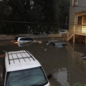 Cars submerged in a parking lot below street level.