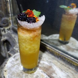 Creative garnish: An ice cup holds aloft berries and edible flowers in the Cocchi Cobbler.