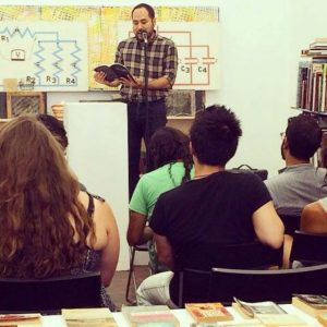 Poet Brandon Som reading at a Sumarr event