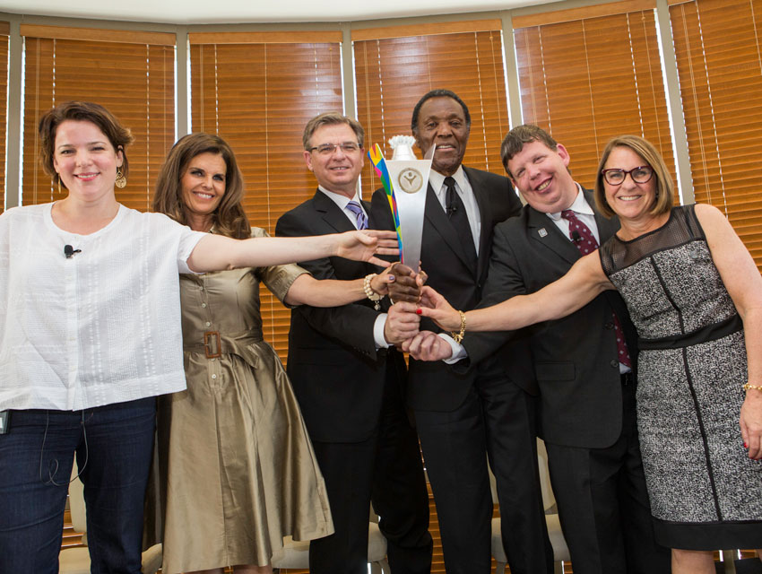 Nancy Miller, Maria Shriver, Patrick McClenahan, Rafer Johnson, Dustin Plunkett, Ann McElaney-Johnson proudly raise the official 2015 World Games Torch