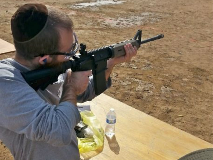 A man in a yarmulke fires an assault rifle at a past event