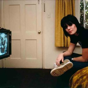 "Joan Jett photographed by Brad Elterman in one of the motel rooms at the Tropicana. ""I will never forget this photo of Joan,"" he says. ""I knew when I took it that it was something special. The setting, the TV with the coat hanger antenna, and, of course, my muse, Joan."""