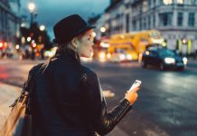 woman waiting for uber rideshare app phone street